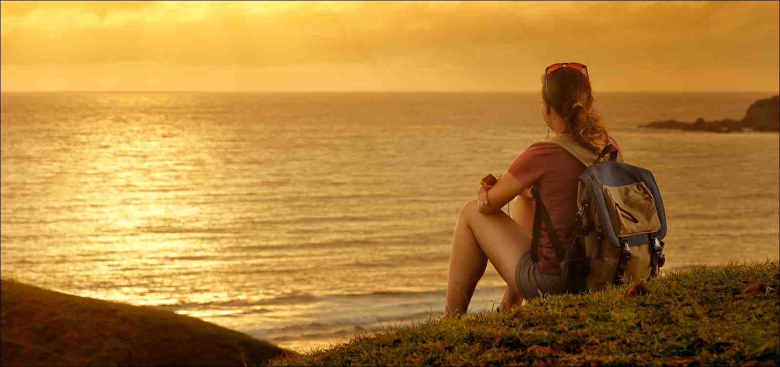 Young traveler with backpack enjoying sunset listening to music near ocean