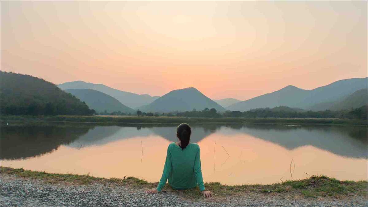 woman sitting by the lake at sunset