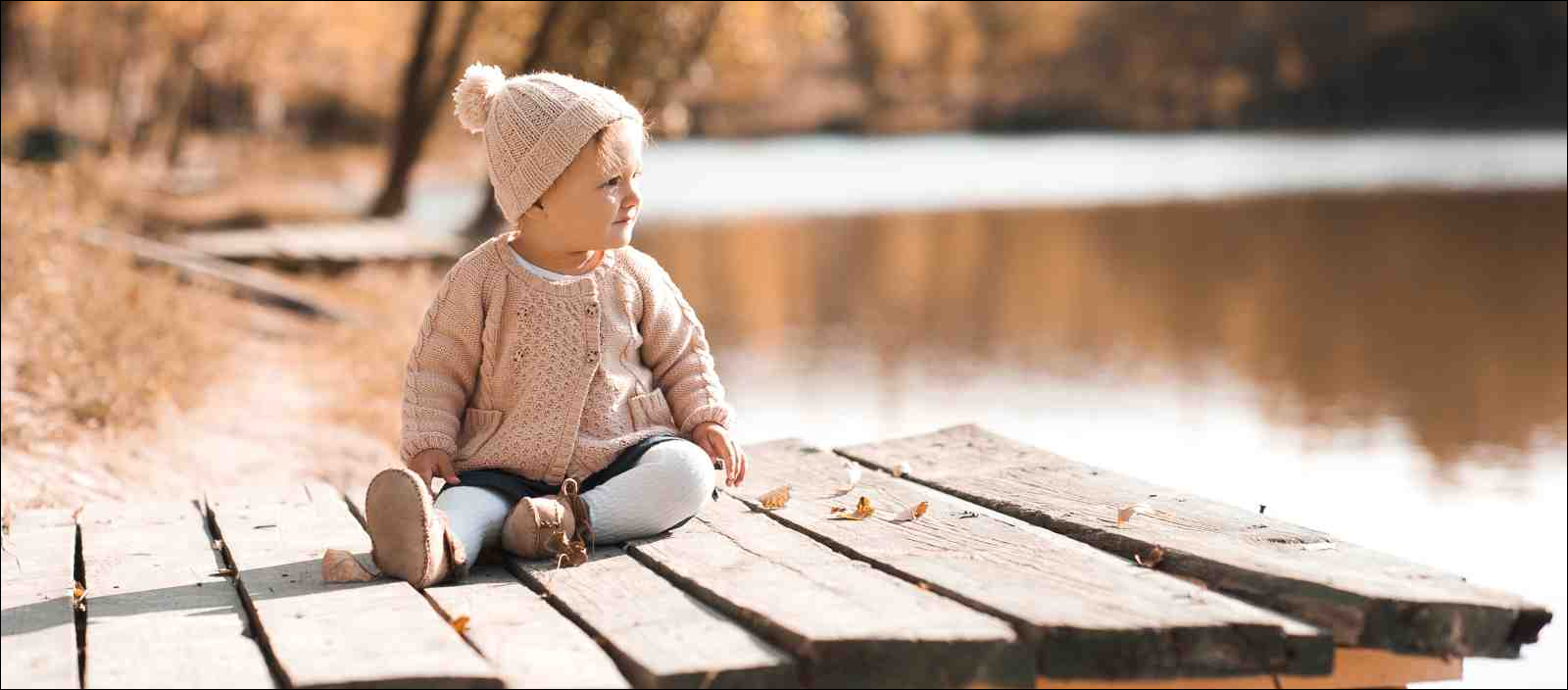1 year old wearing knitted autumn clothes sitting in park