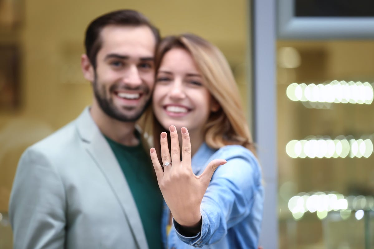 Engaged man and woman smiling with the woman showing off her engagement ring