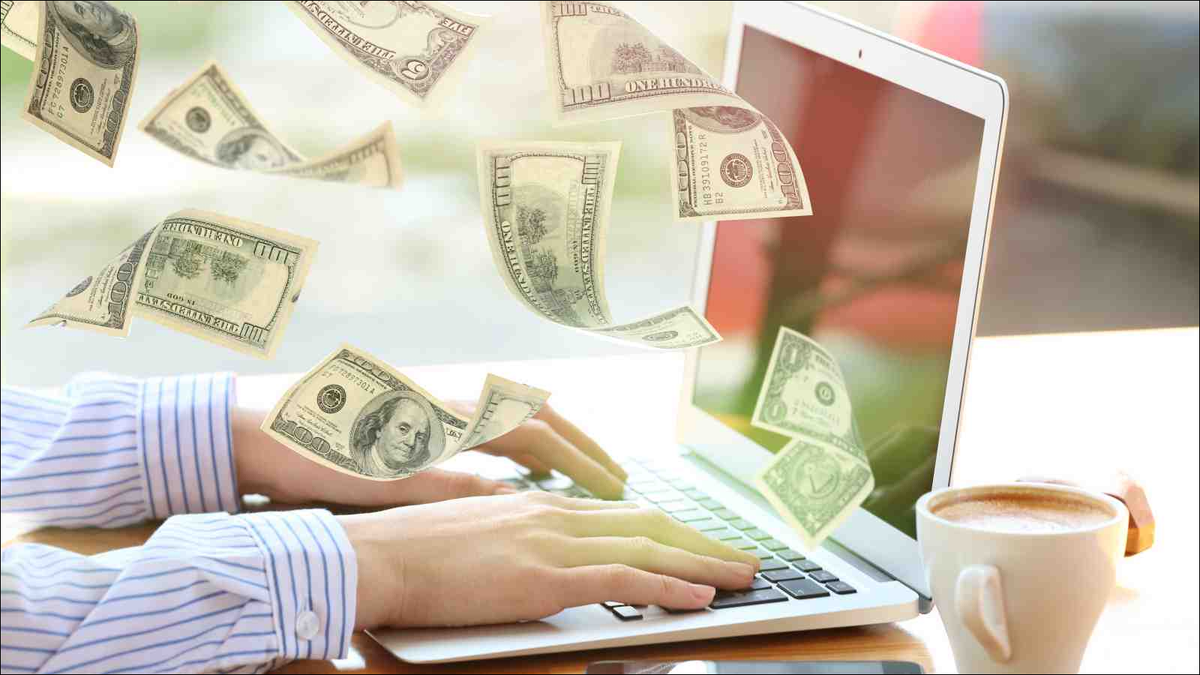Money flying out of laptop while woman using it at table in office