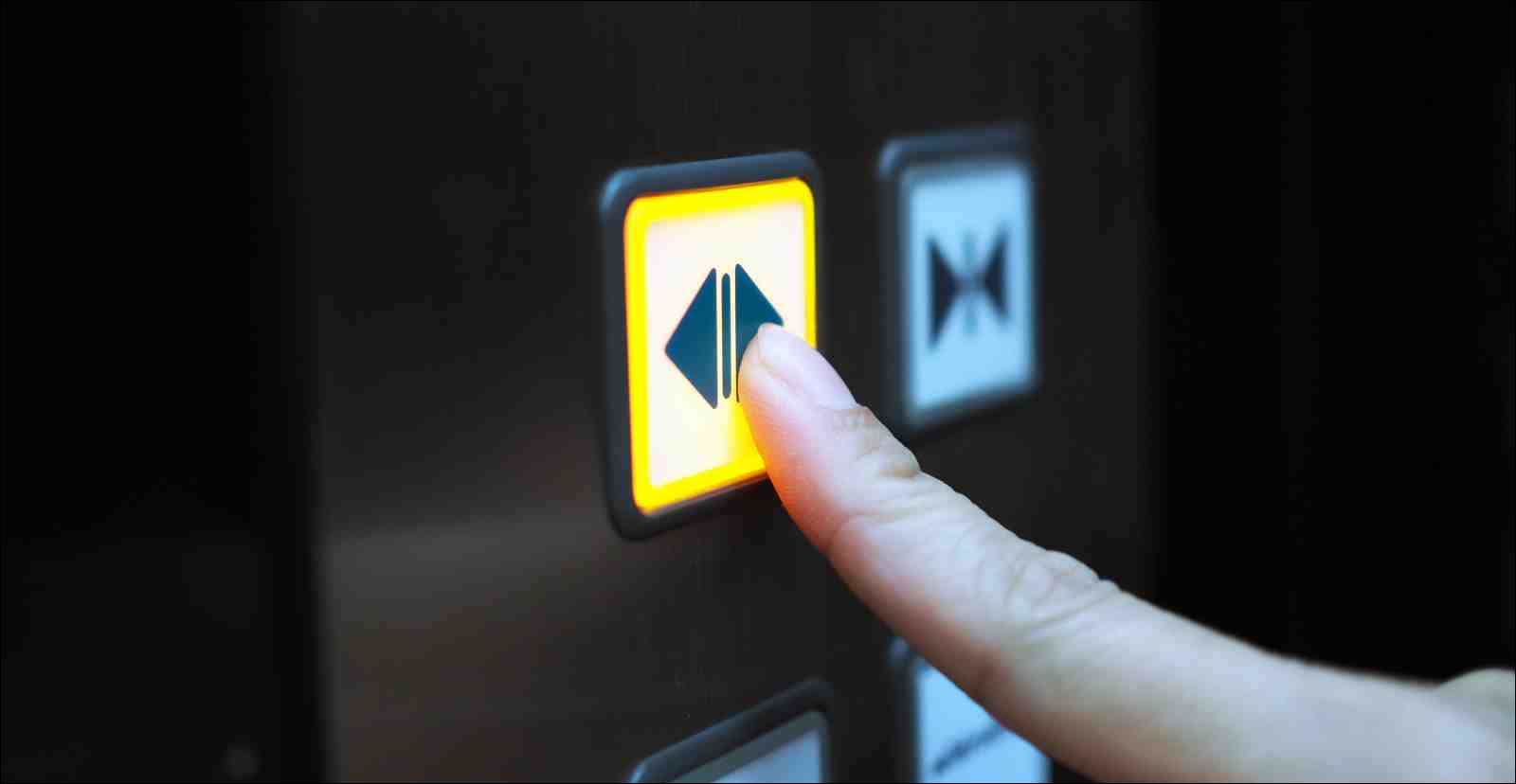 woman's finger pressing hold open button in elevator