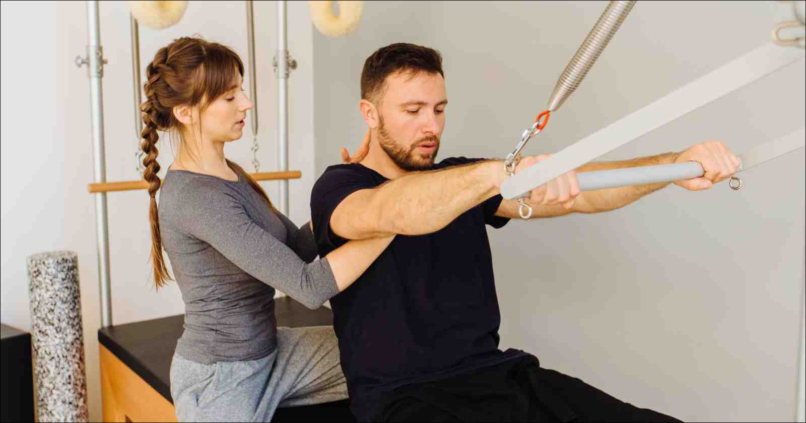female instructor of pilates helping beard man workout in cadillac bed