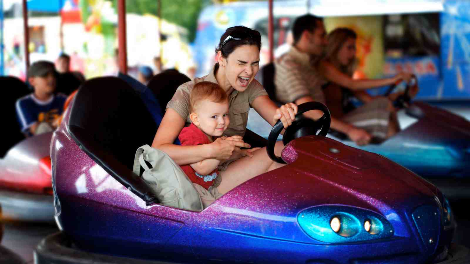 mother and toddler in bumper car at theme park