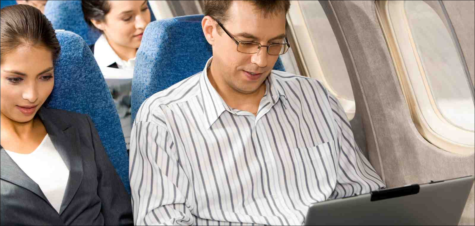 man and woman typing on laptops during flight