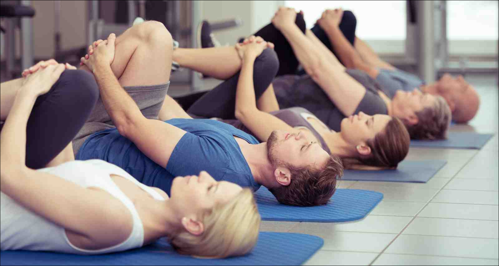 group of people in a gym class lying in a receding row on mats doing leg flexes
