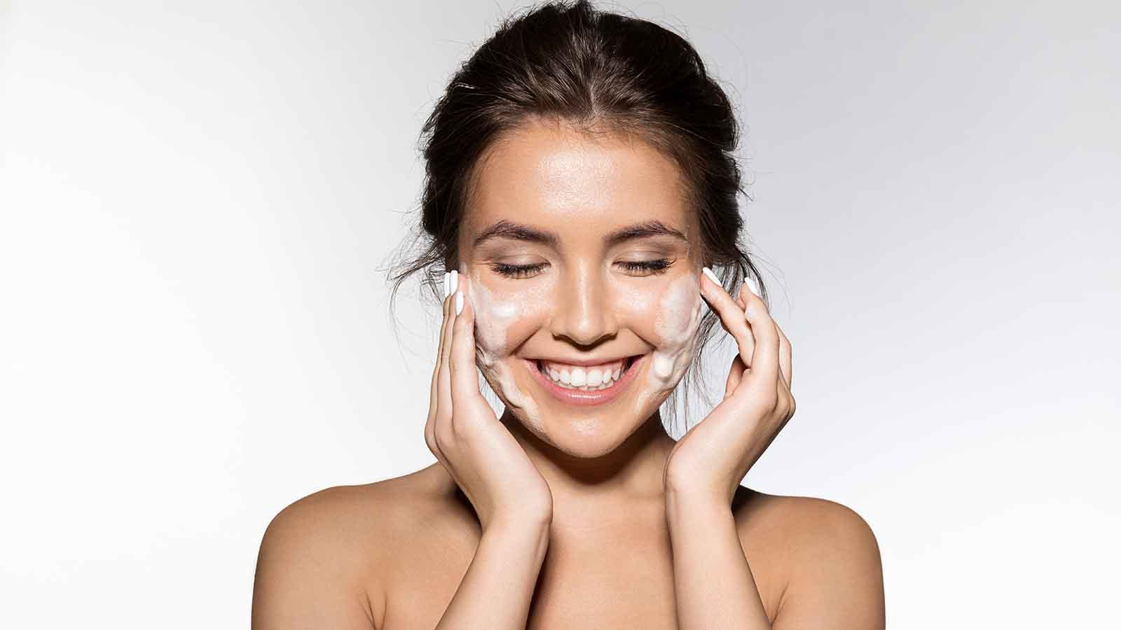 woman washing her face with a foaming cleanser