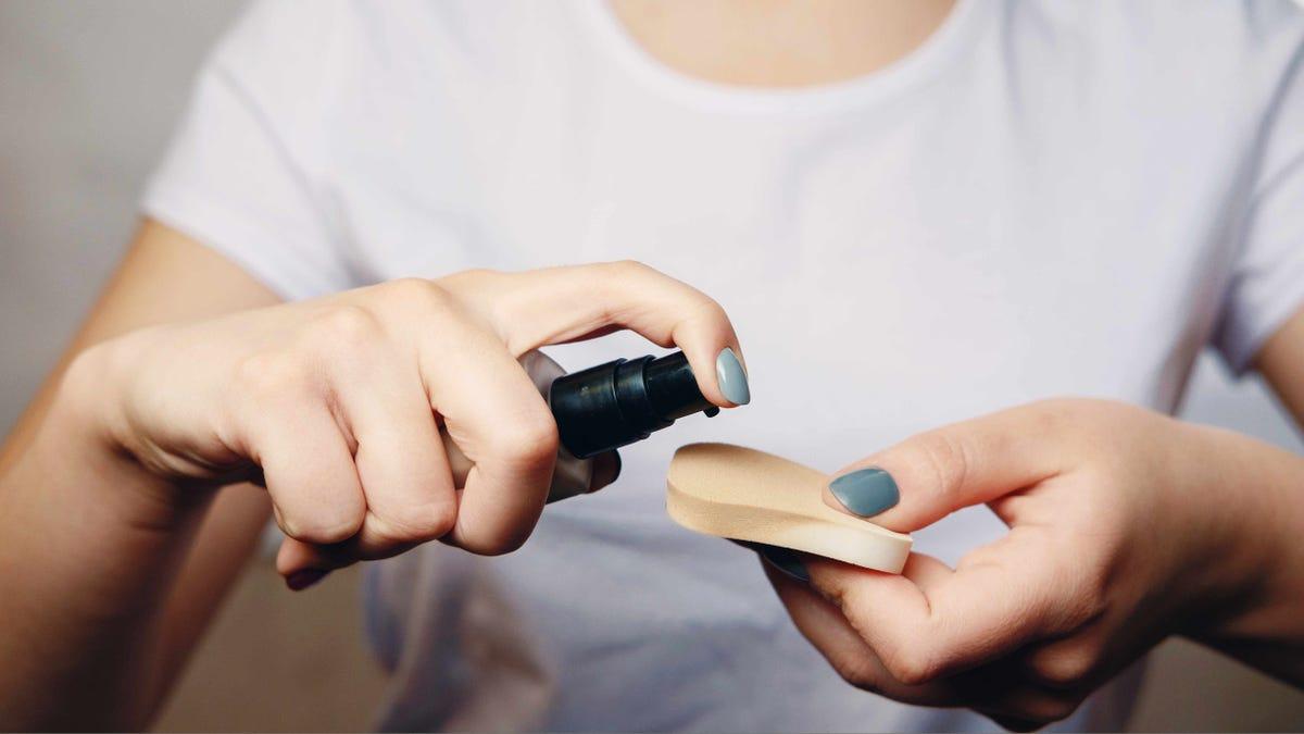 woman putting foundation makeup on a sponge