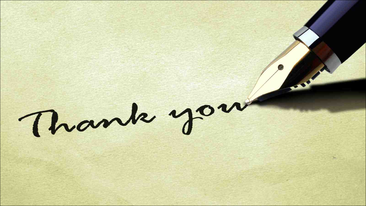 closeup of fountain pen writing thank you on textured paper