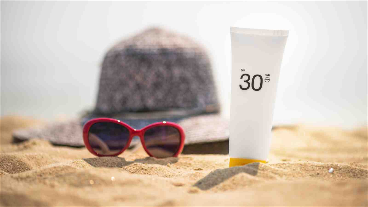 Bottle of sunscreen lotion on the sandy beach