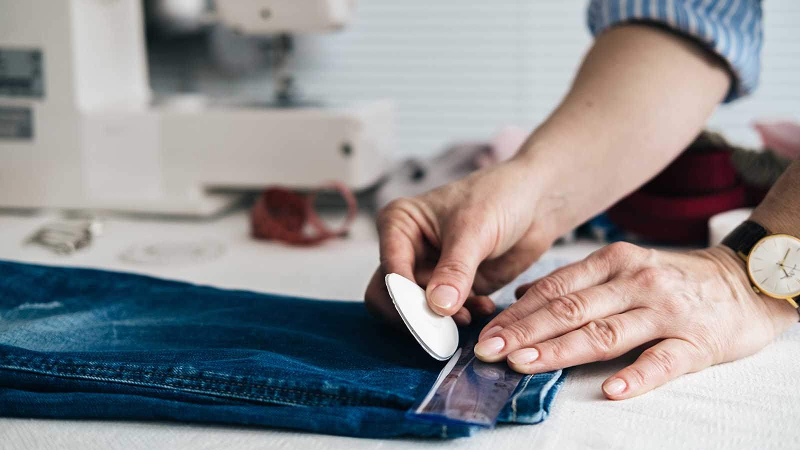 Tailor hemming a pair of blue jeans