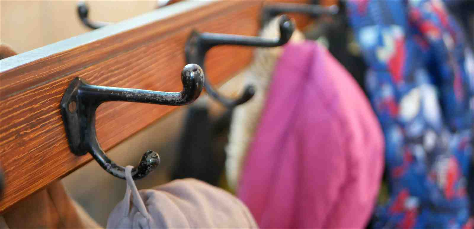 Coat rack with several hooks and coats hanging from them