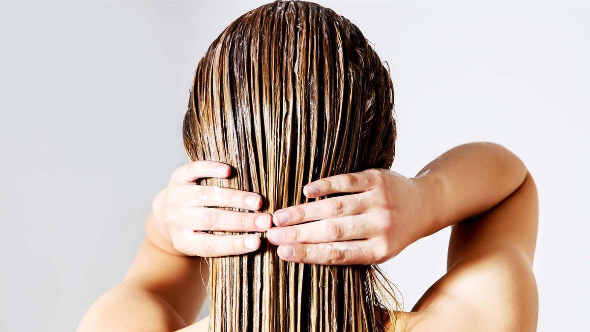 Woman apply a hair mask at home