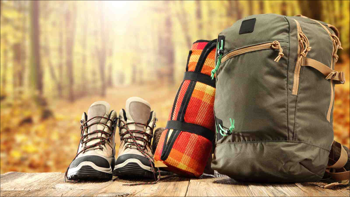 hiking boots, backpack, and other gear on wood deck on sunny day