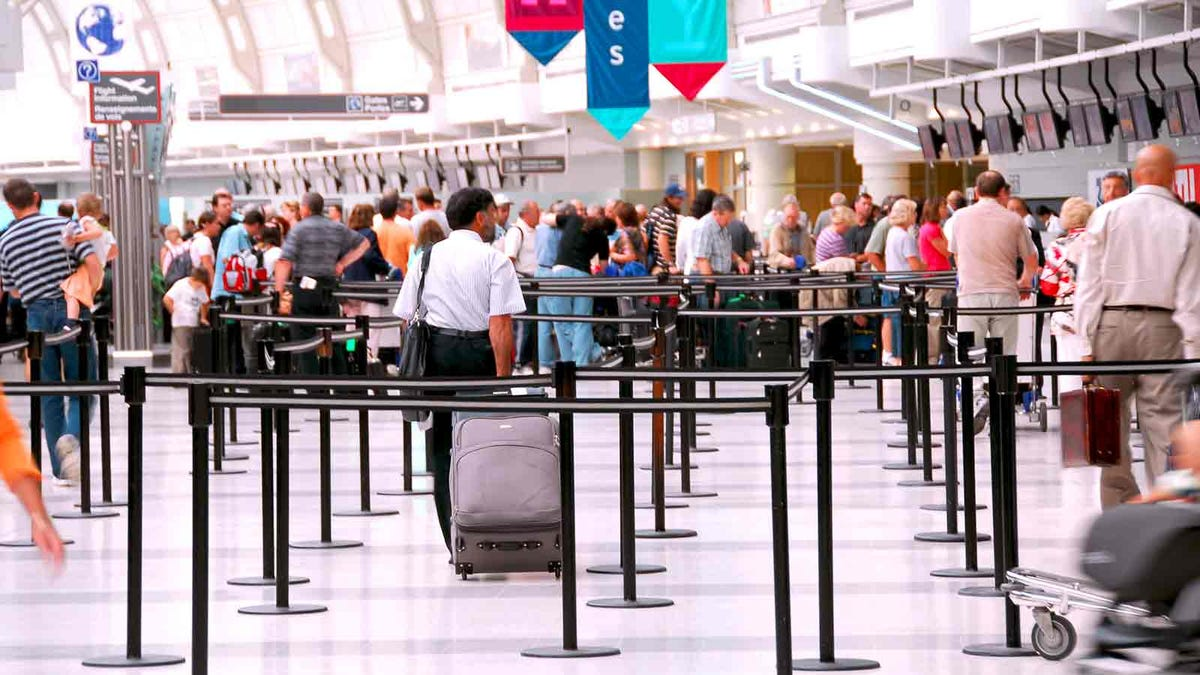 Passengers lining up at a check-in counter at the airport