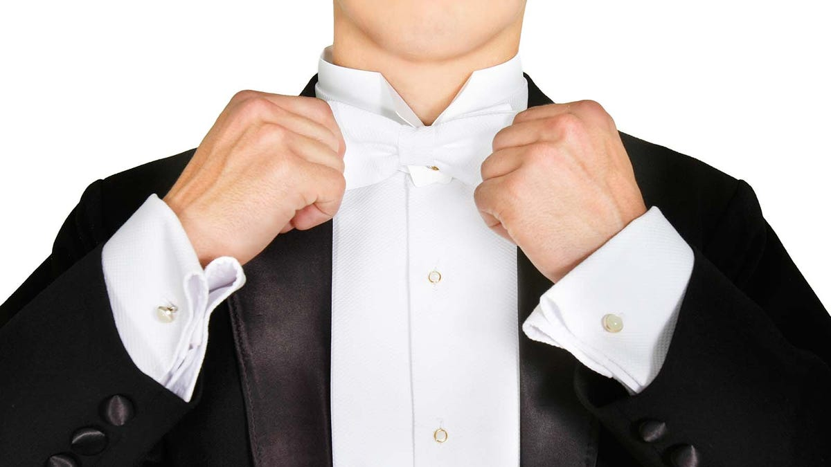 Man tying a white bow tie for formal white tie dress