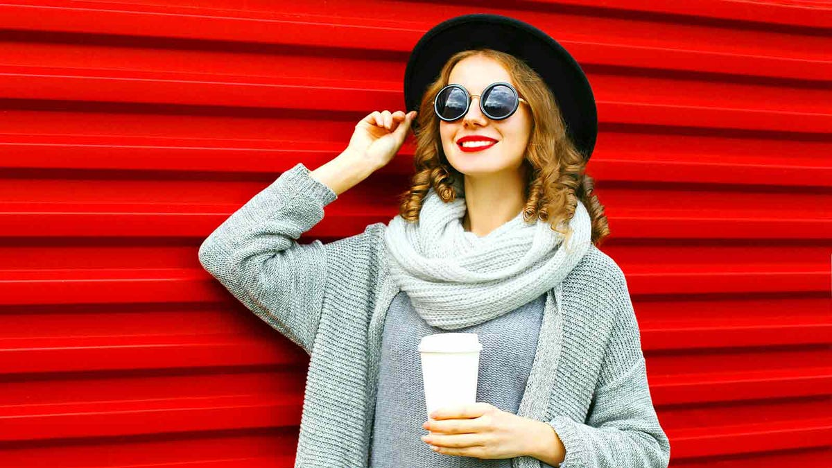Young woman wearing stylish sunglasses and a fashionable outfit holding a cup of coffee