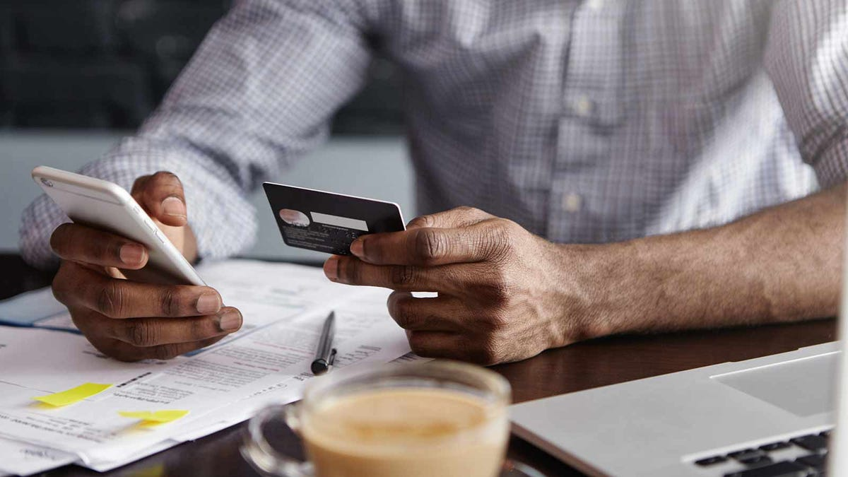 Man holding bank card while reviewing bills and checking statements