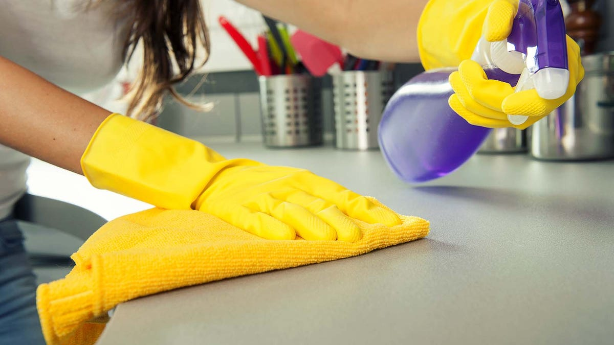 Woman wiping down her counters with a microfiber rag and sanitizer