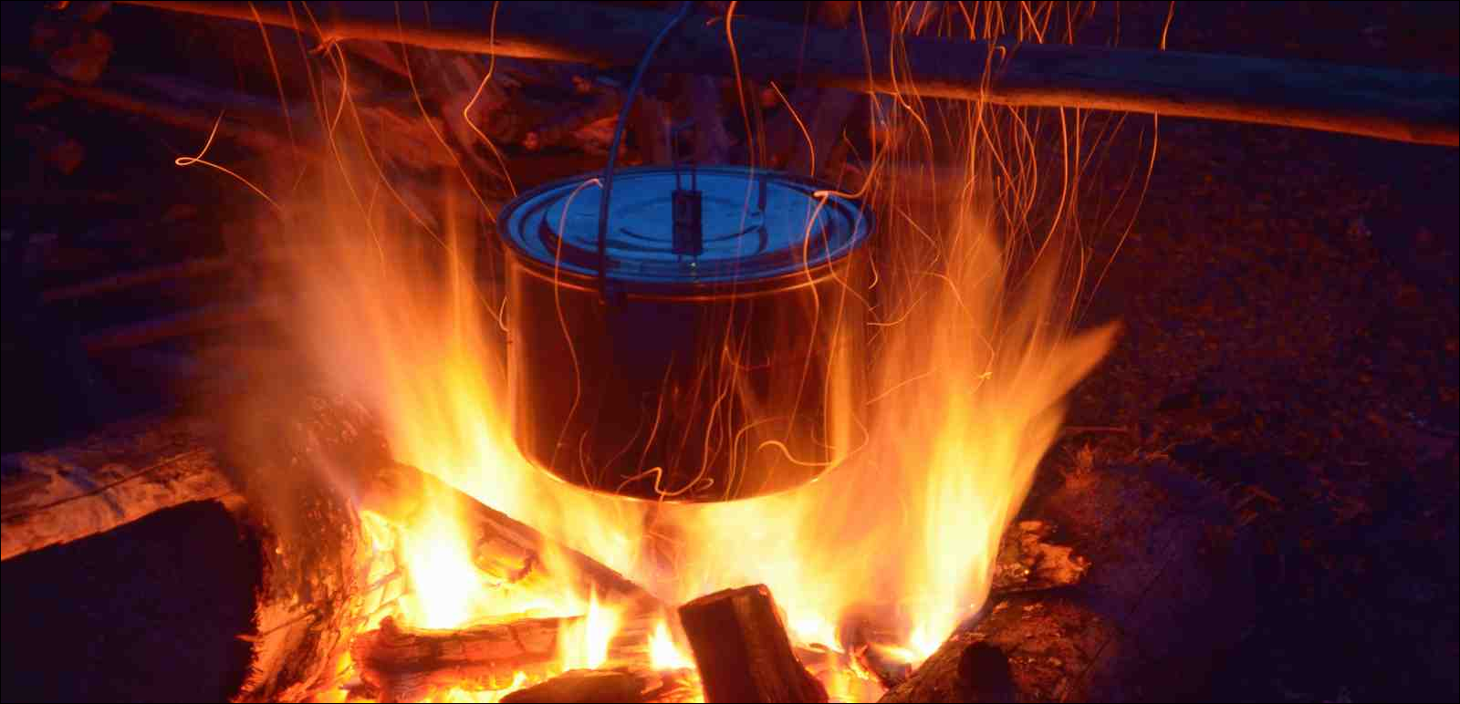 kettle over camp fire in the evening