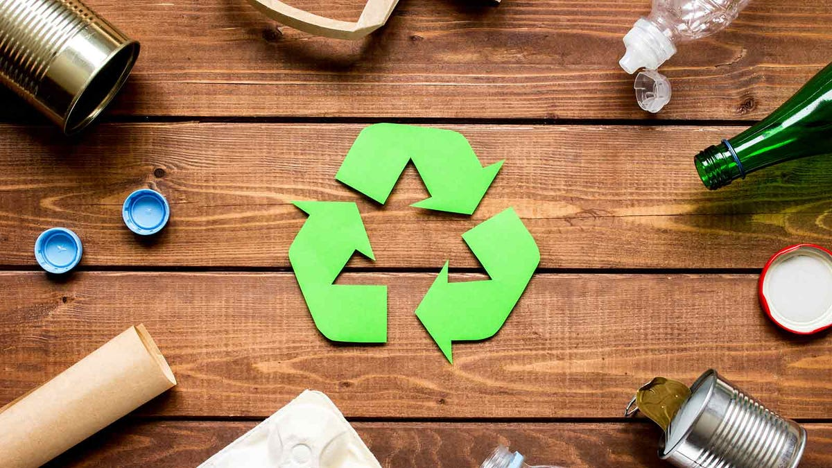 recycling symbol on wood table surrounded by various recyclable products