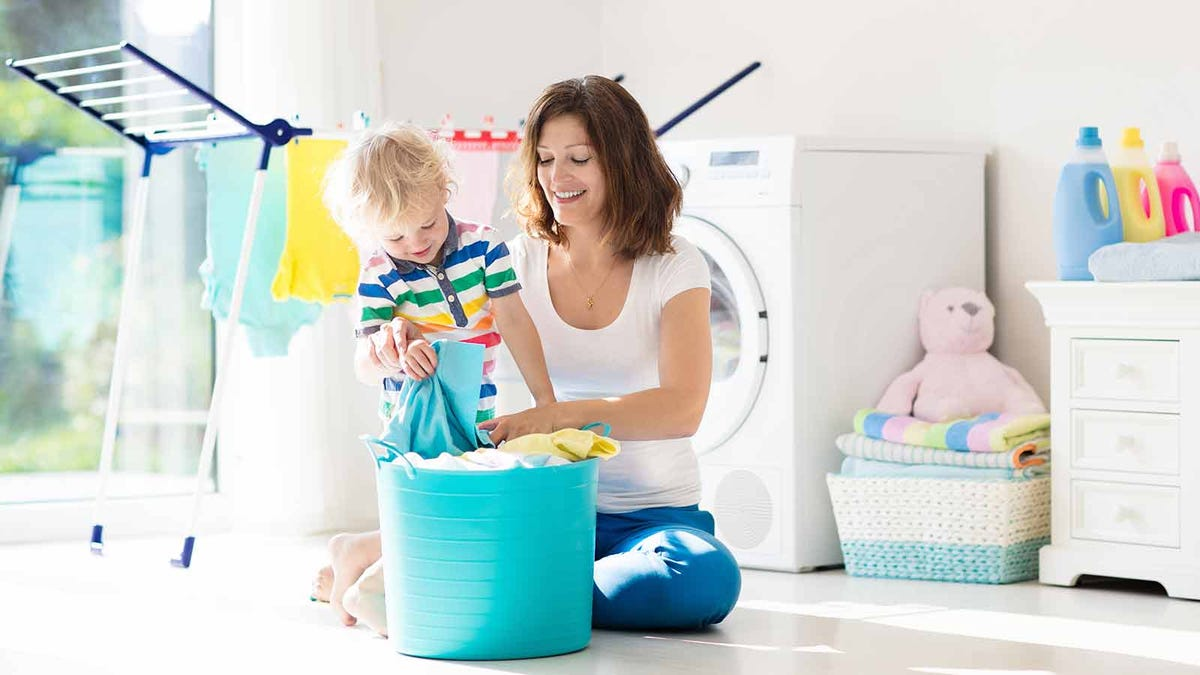 Mother sorting fresh laundry with her toddler in a sunny laundry room