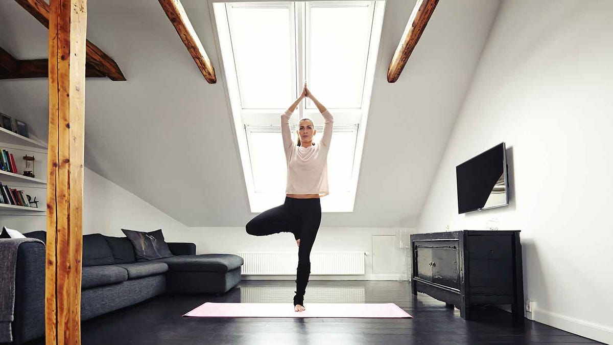 Woman on a yoga mat in tree pose, standing in a sunny living room