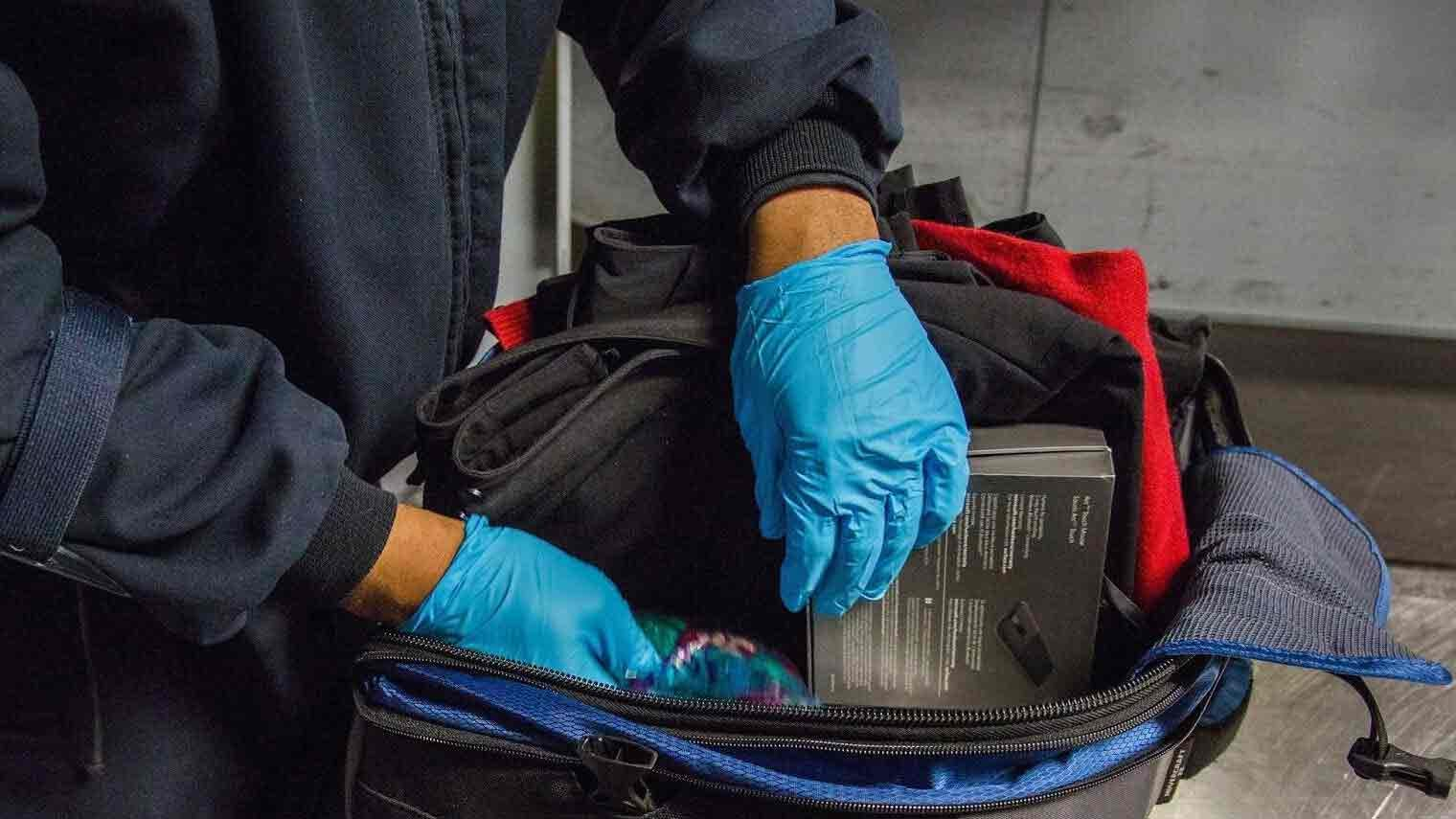 TSA agent examining the contents of a carry on bag