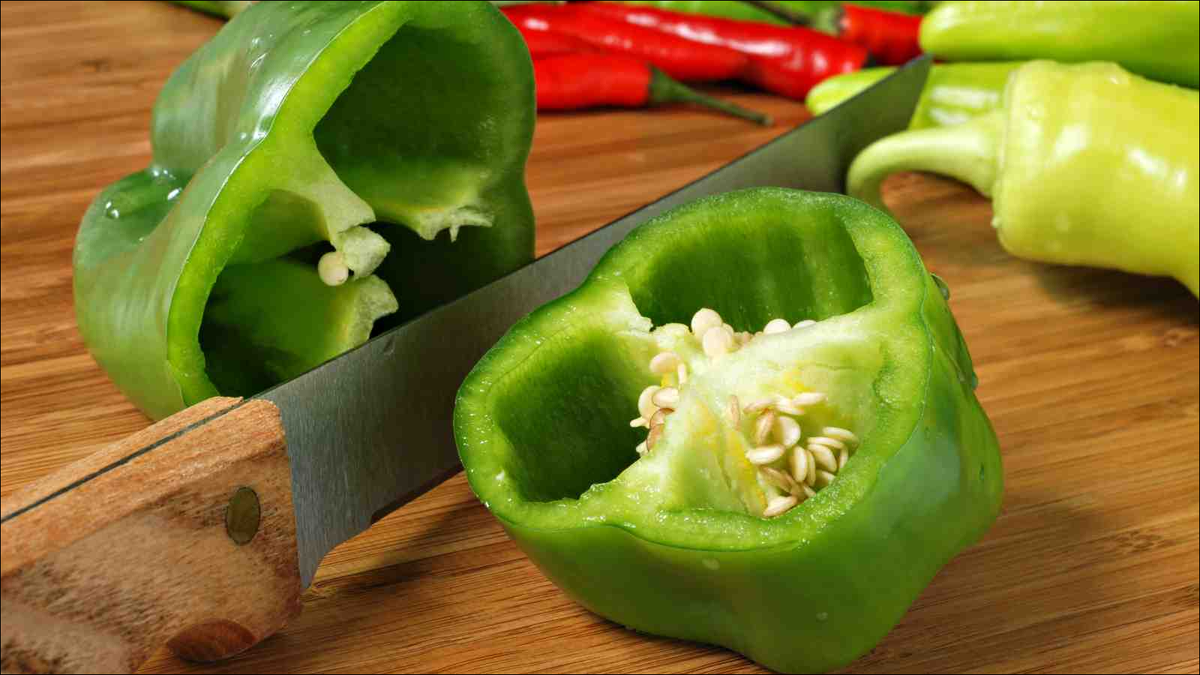 Green bell pepper with knife on bamboo cutting board
