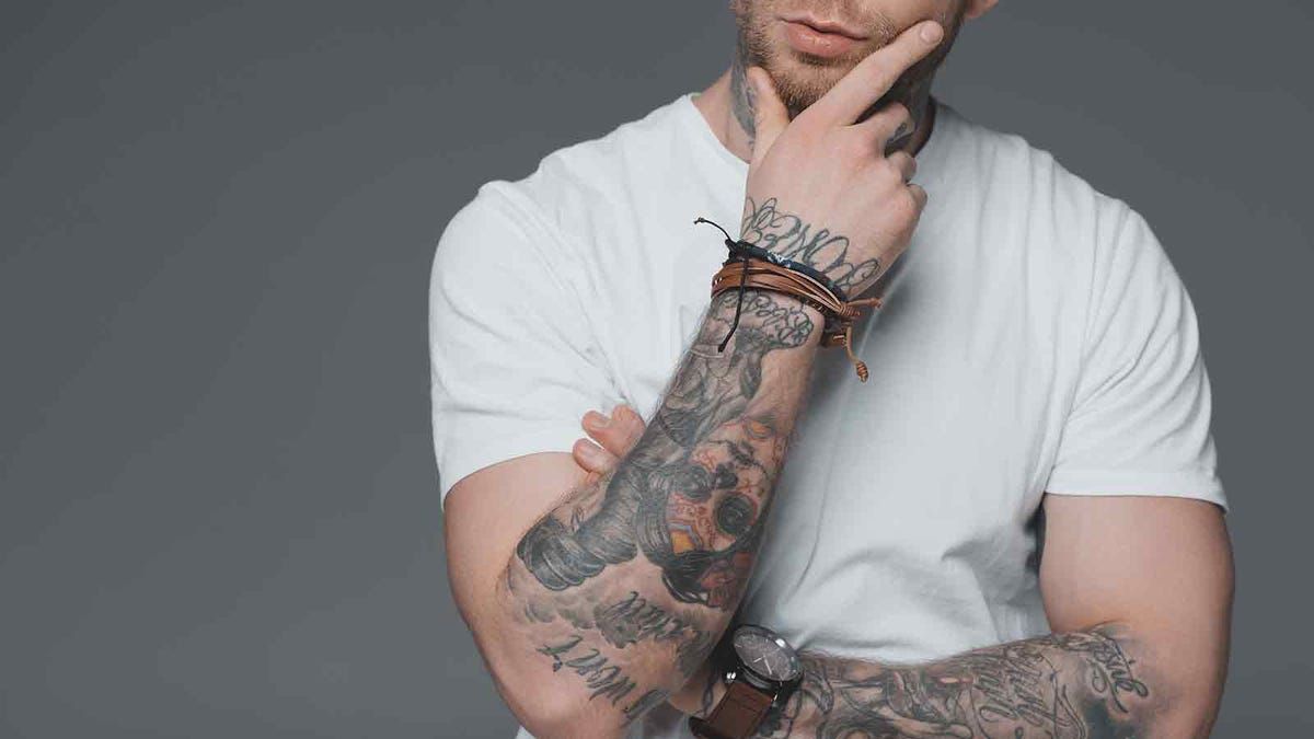 Man with tattoos, touching his chin thoughtfully
