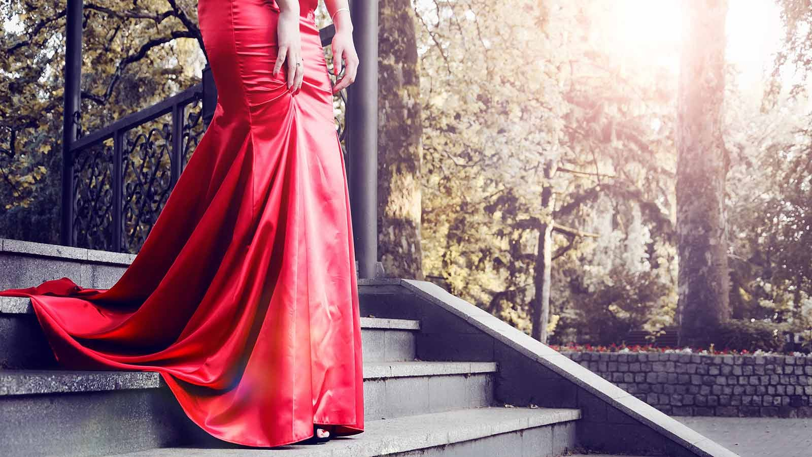 woman descending a staircase outdoors in a beautiful long red satin dress