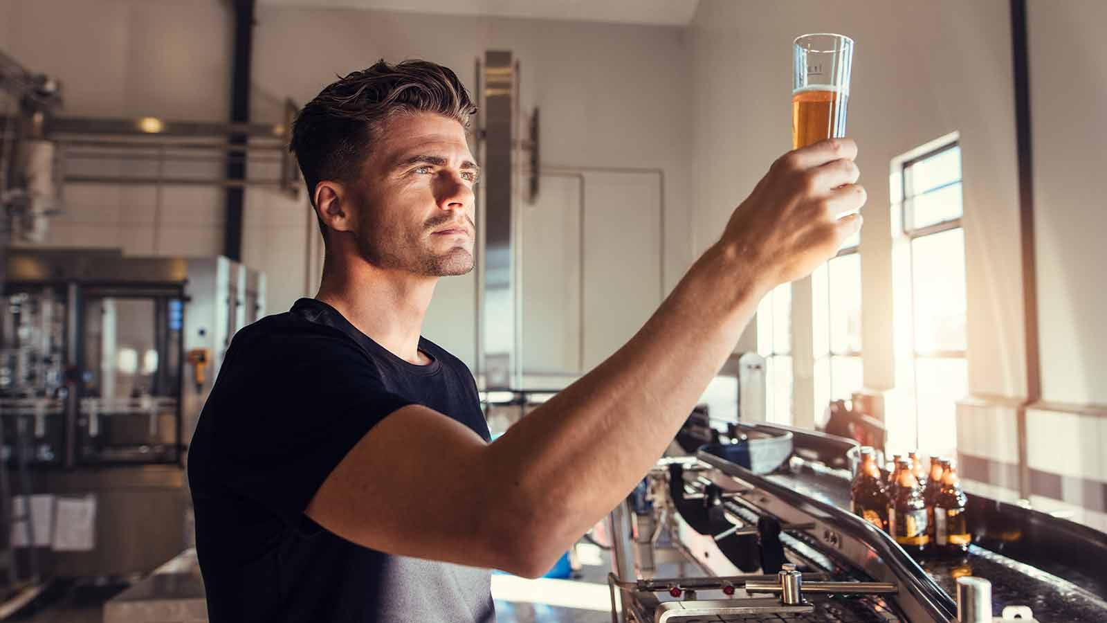 Man examining freshly brewed beer