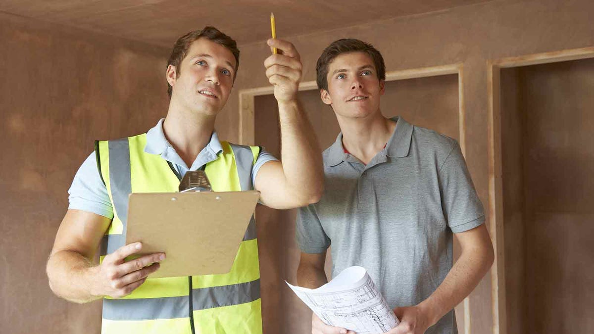 Man stands with a home inspector, who is discussing the the state of the home with him
