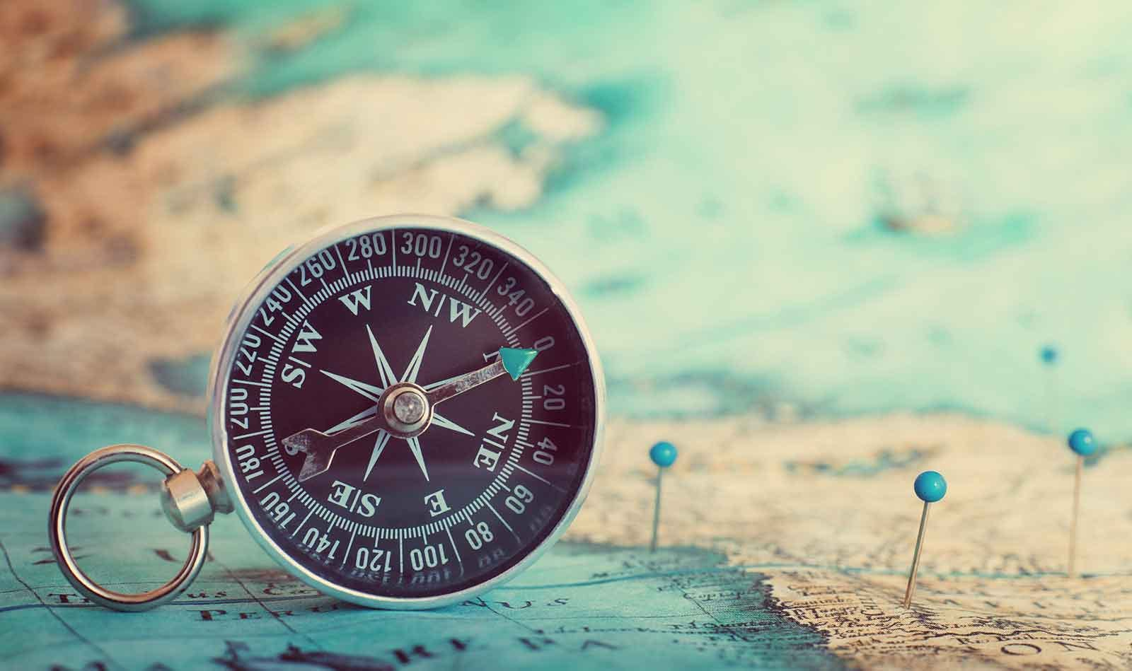Compass resting on a map with destinations marked by pins