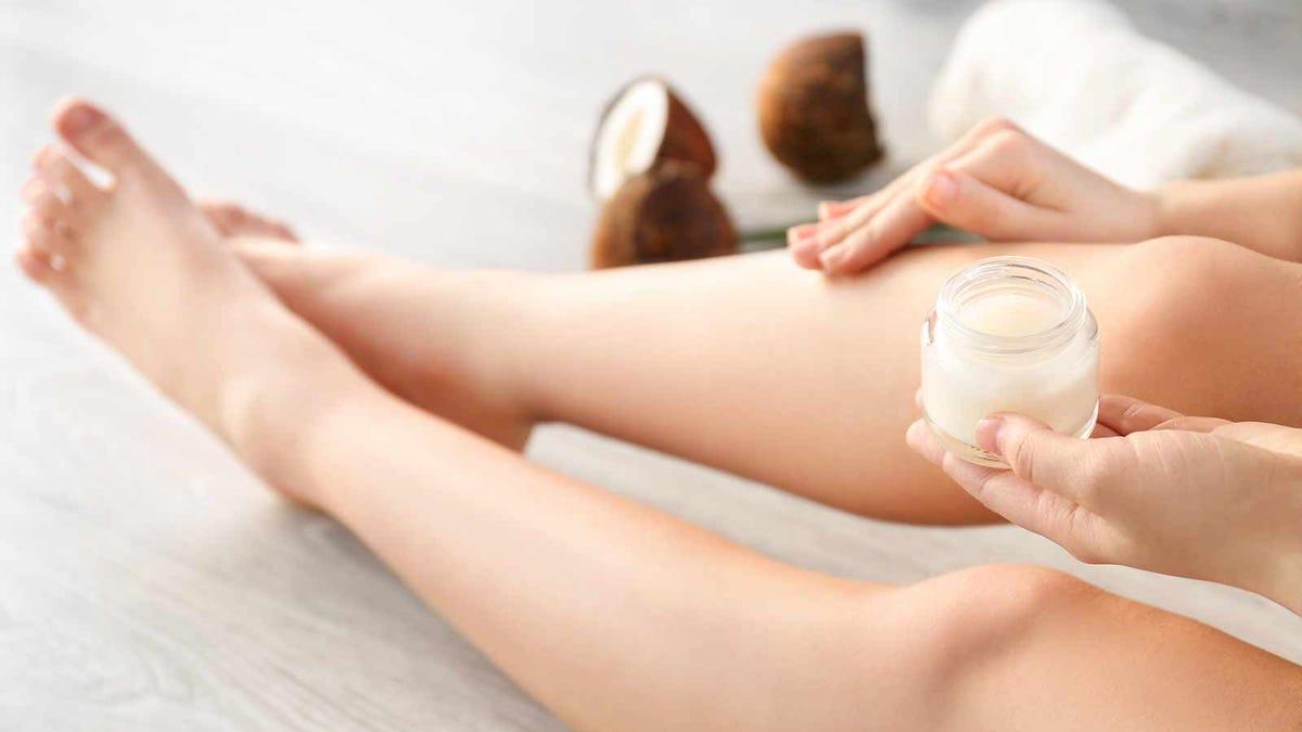Woman applying moisturizing cream to her legs