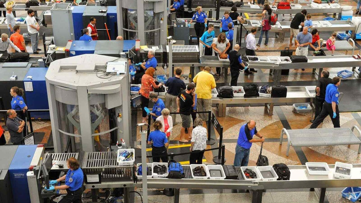 Busy security line at an airport with numerous travelers and security agents