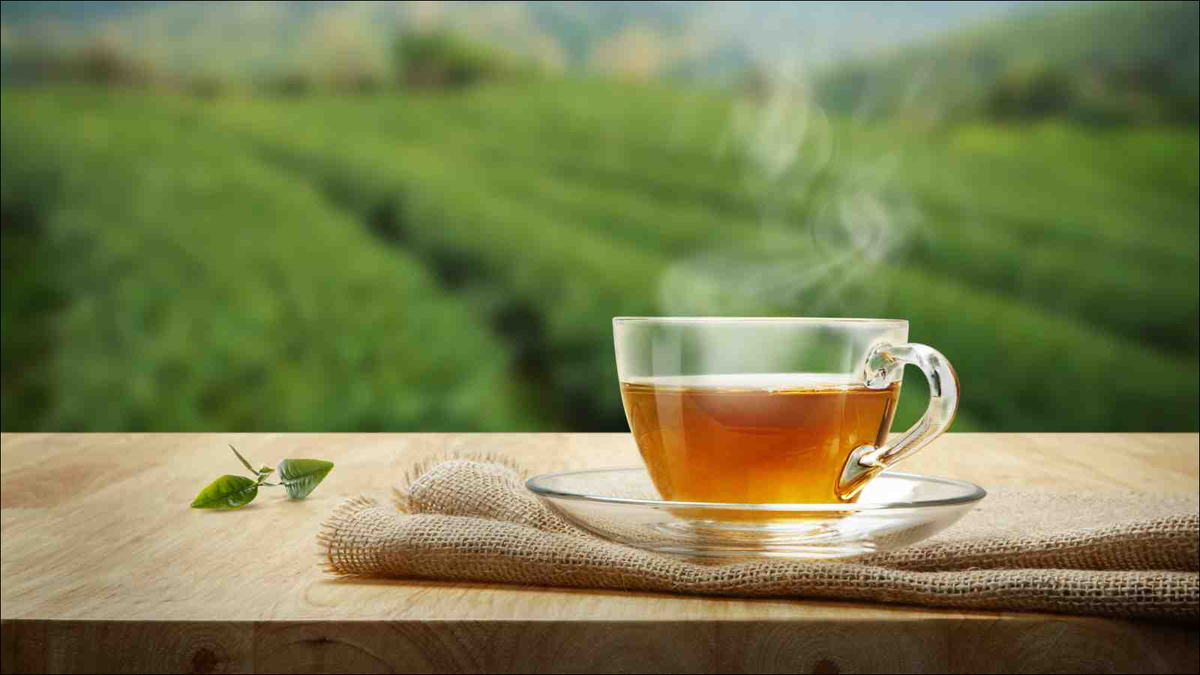 Tea cup with green tea leaf on the wooden table outdoors