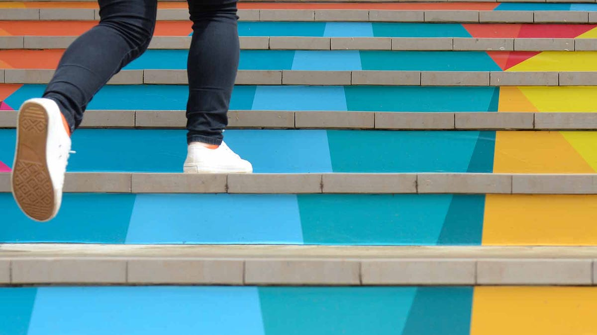 Bottom of a woman's legs in leggings and sneakers running up a colorful staircase.