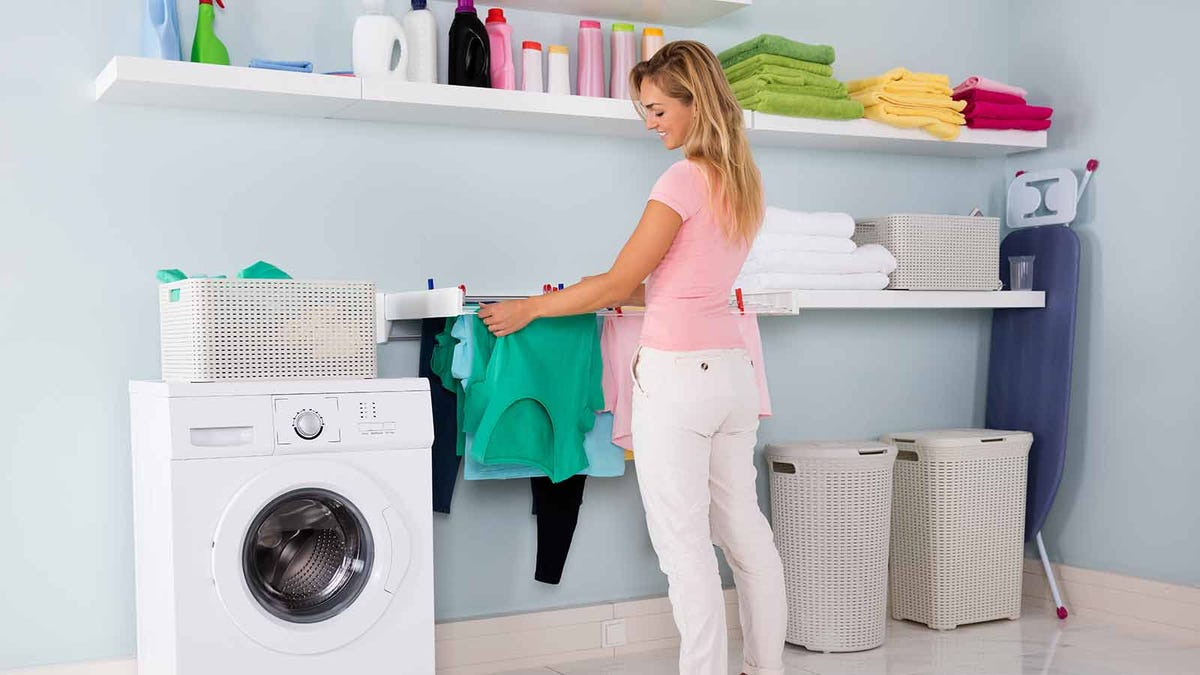 Woman putting clothing on a wall-mounted drying rack