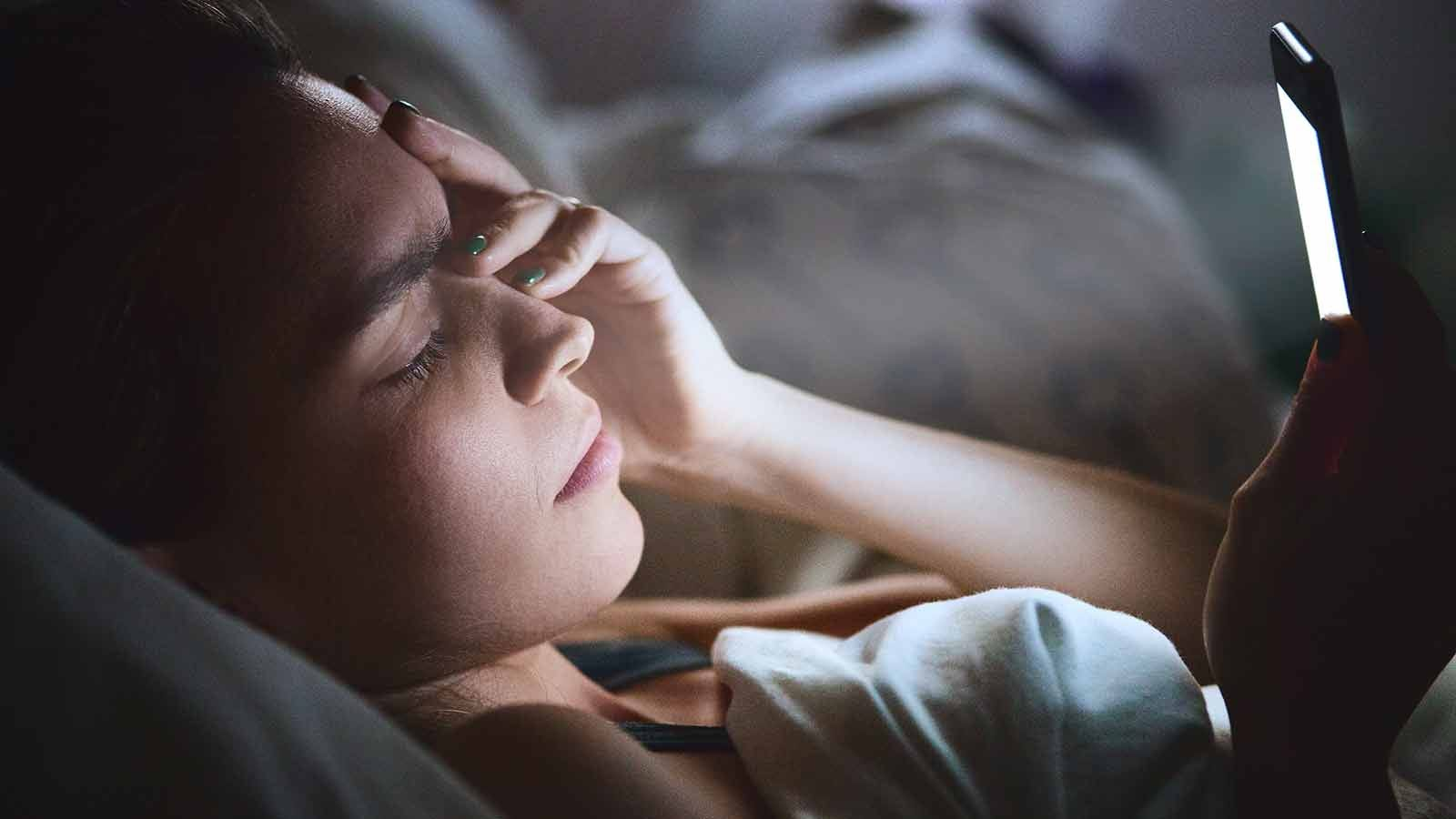 Woman looking at her phone in the middle of the night