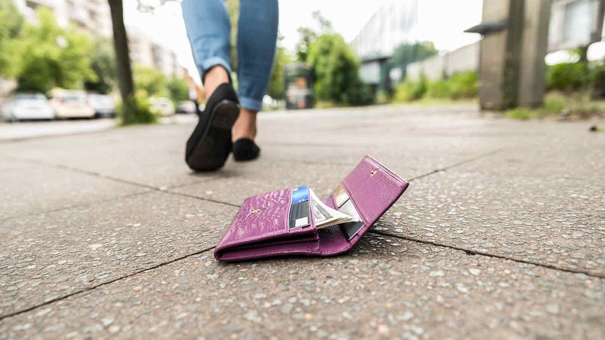 Woman walking away after unknowingly dropping her wallet on the street