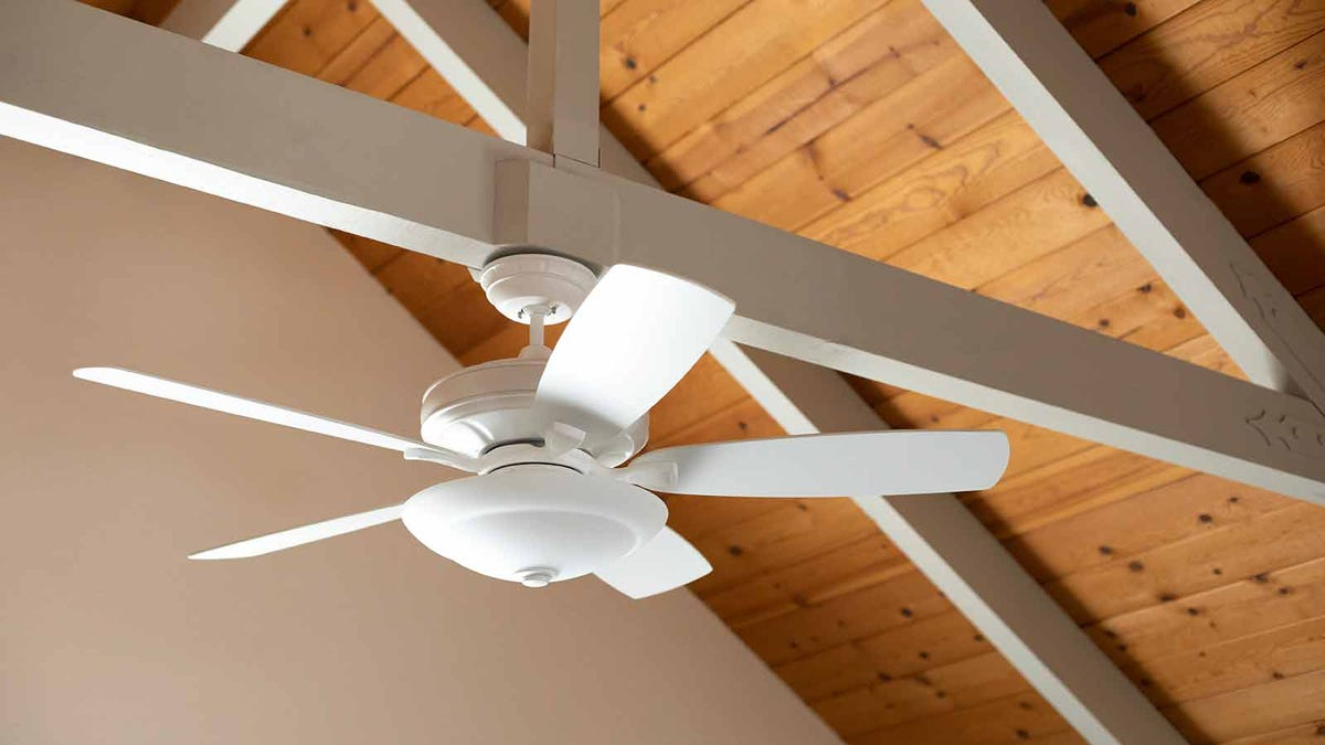 White ceiling fan hanging from a support beam in a vaulted living room