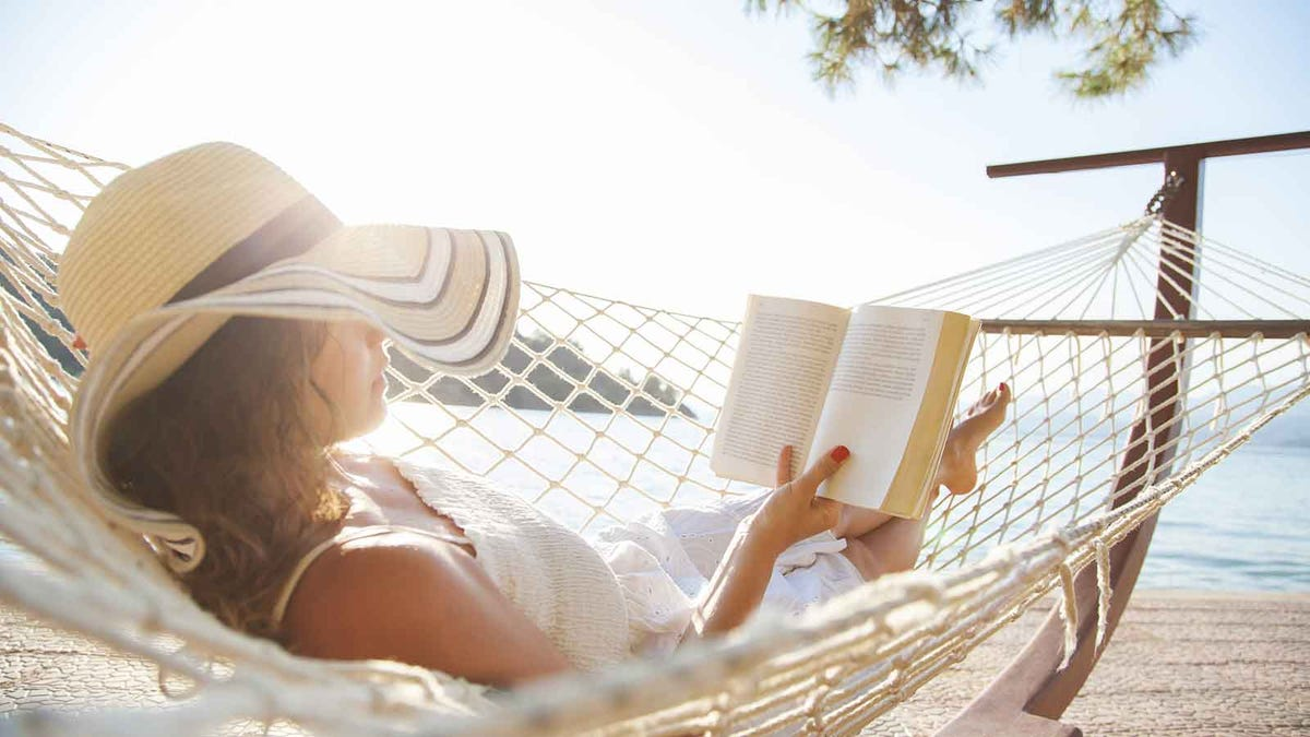 Woman relaxes in a hammock reading a book from her summer reading list