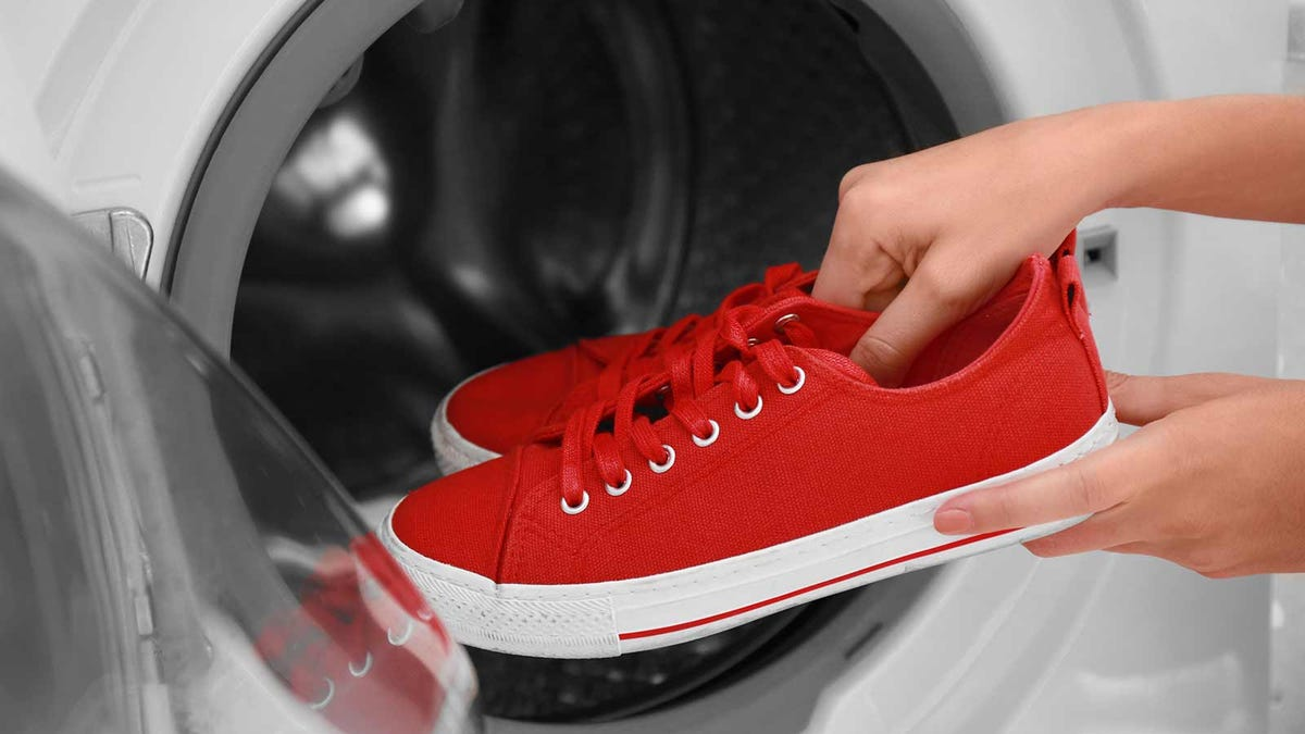 Woman's hands putting red canvas shoes in a front loading washing machine