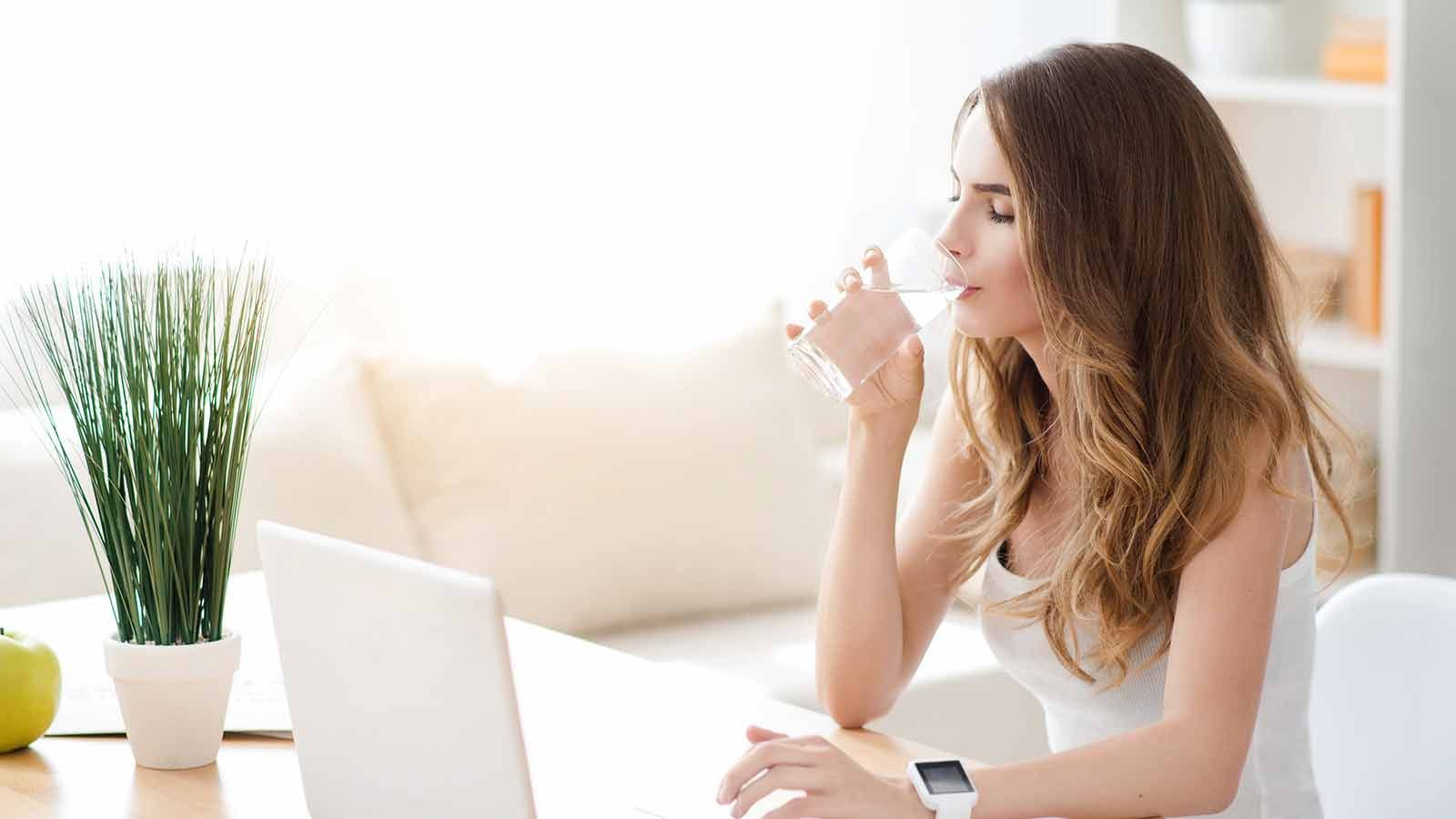 Woman drinking water in a sunny living room