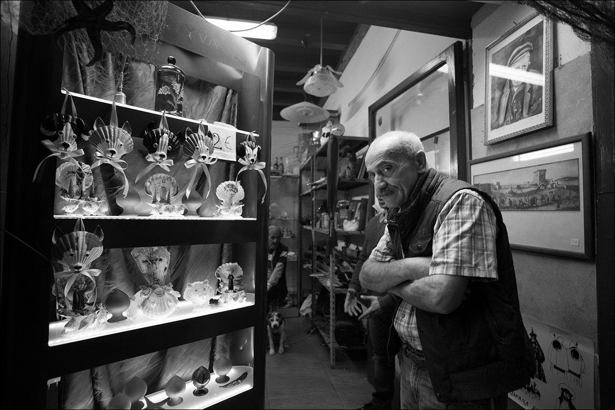 An Italian man in a shop standing in front of a shelf of trinkets and glass figurines.