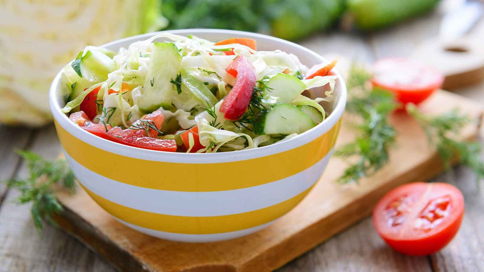 Fresh salad in a white and yellow striped bowl sitting on a cutting board.