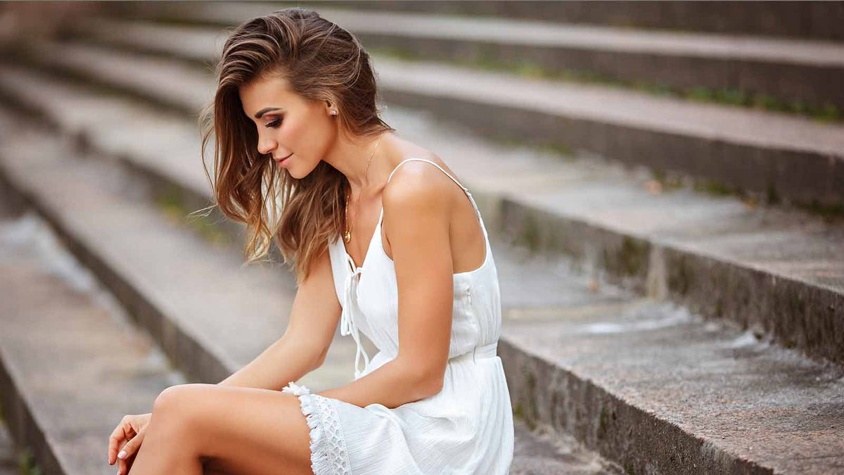 Tan woman sitting on outdoor cement stairs.