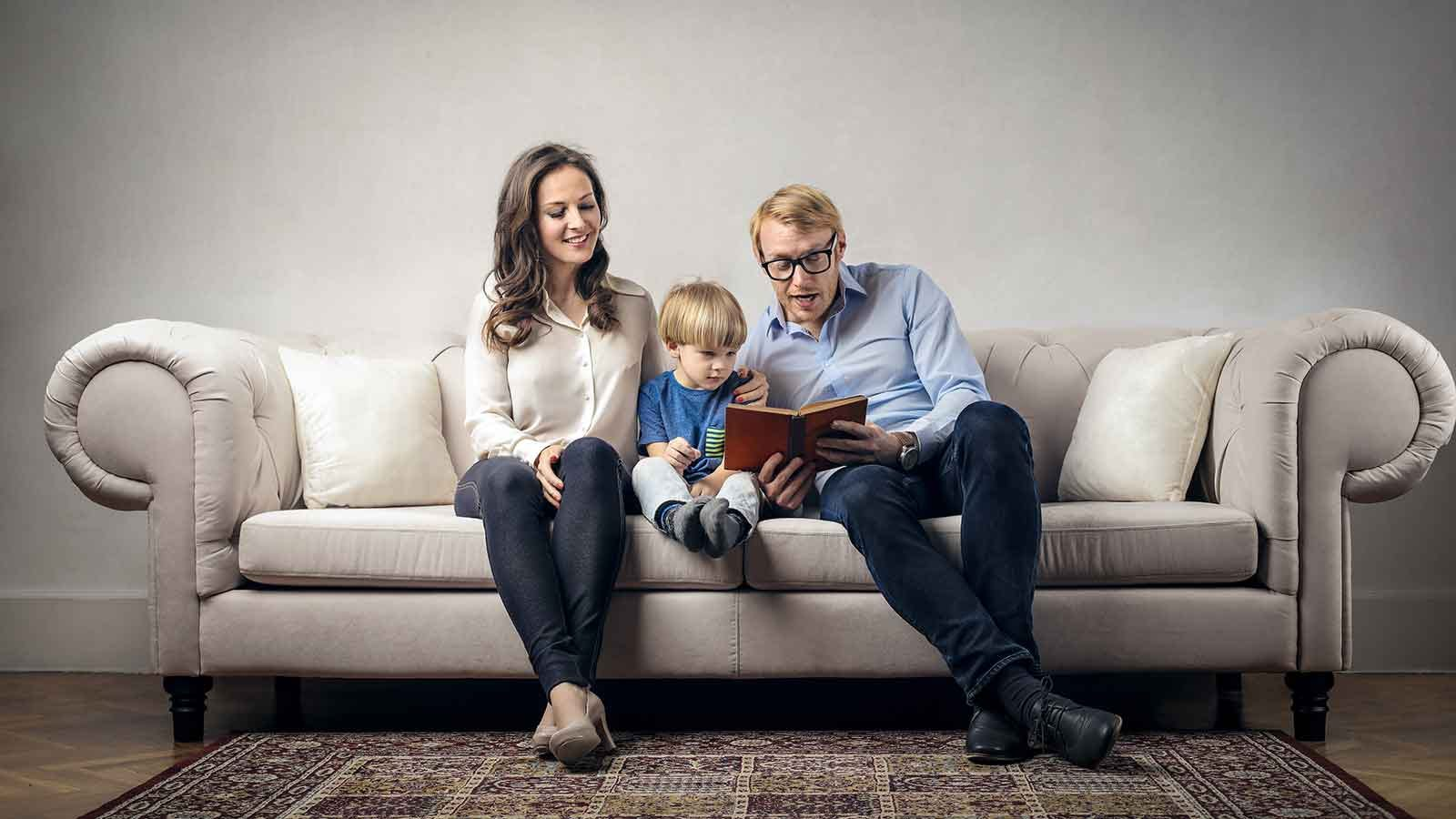 Family reading a book together on the couch.