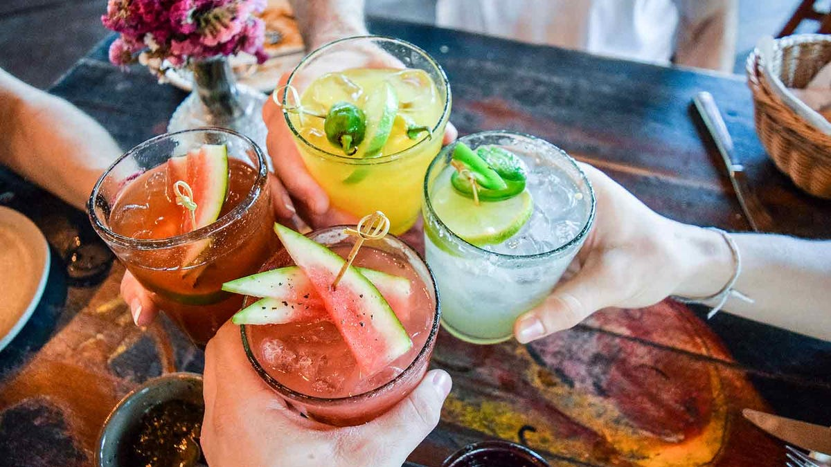 Friends toast with some summer cocktails